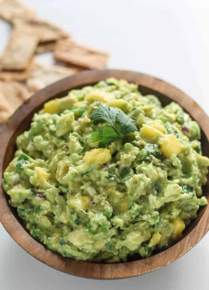 Mango Tomatillo Guacamole | Destination Delish - Roasted tomatillos give this guacamole a punch of tangy, citrus flavor for a unique twist on the traditional guacamole