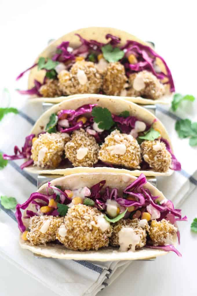 Crispy Cauliflower Tacos | Destination Delish - healthy tacos bursting with flavor and texture thanks to the crispy baked cauliflower, tangy slaw, and spicy chipotle cream
