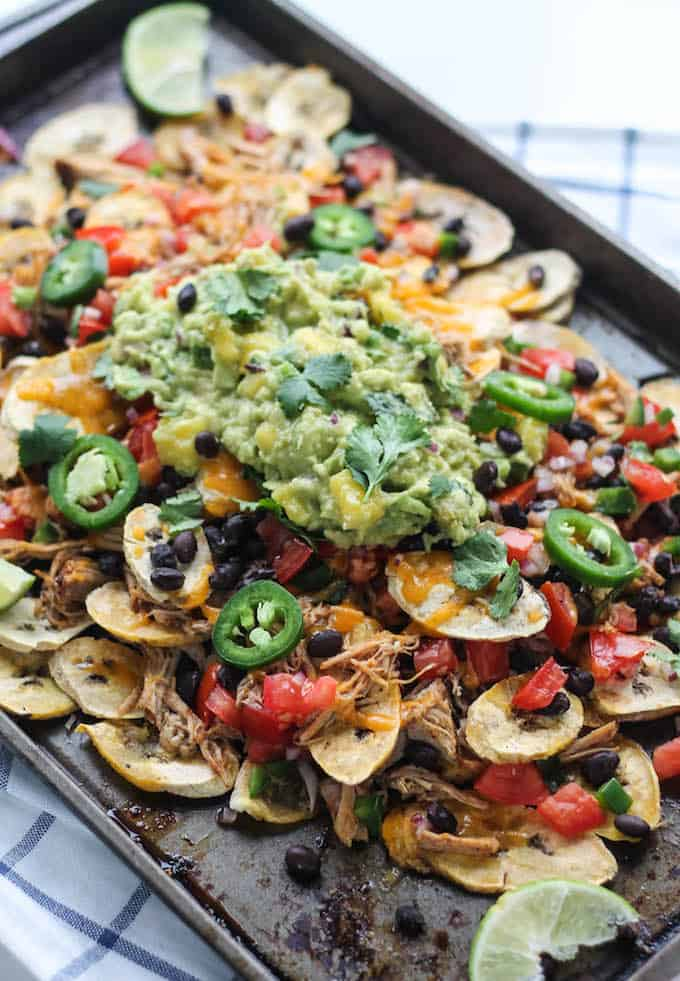 Pulled Pork Plantain Nachos | Destination Delish - healthier nachos using baked plantain wedges topped with tender pulled pork, black beans, and all your fave toppings!