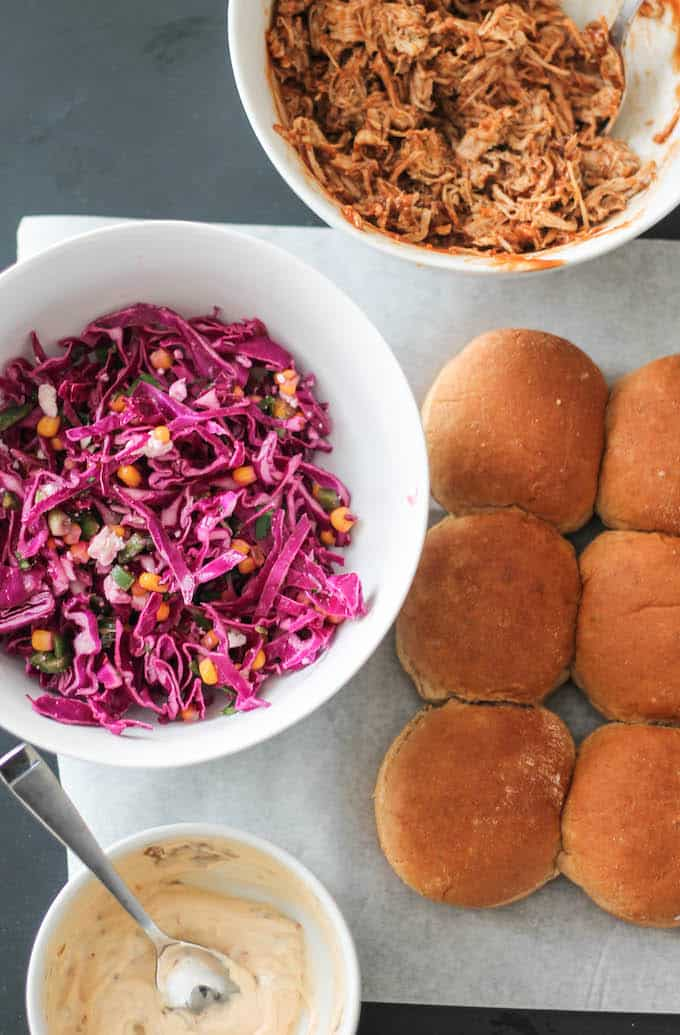 Southwest Pulled Pork Sliders | Destination Delish - mini sandwiches packed with flavor from the boldly seasoned pulled pork, corn and jalapeño slaw, and spicy chipotle mayo.