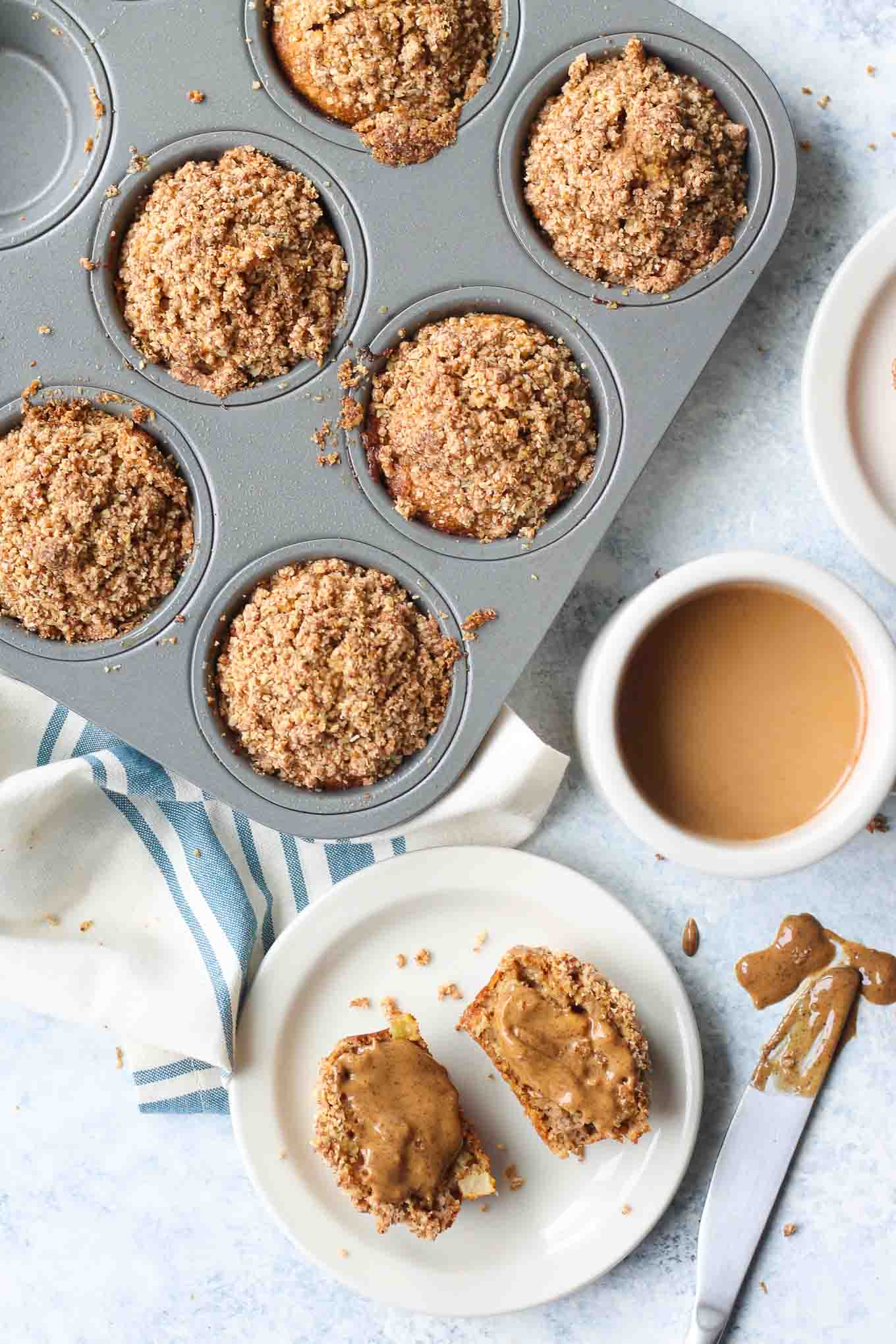 Muffins in the tin with a cup of coffee and almond butter spread on a single muffin