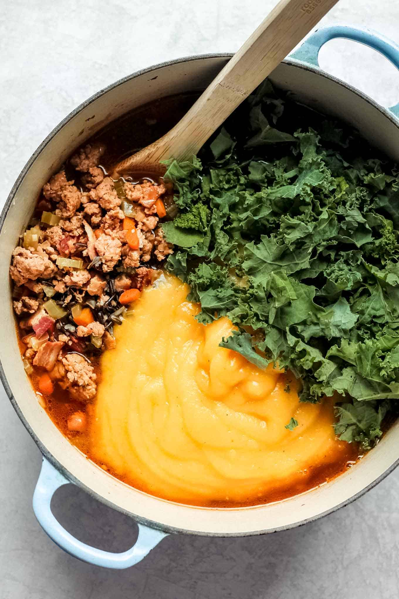 The wild rice and sausage mixture, kale, and pureed butternut squash in the pot prior to mixing together.